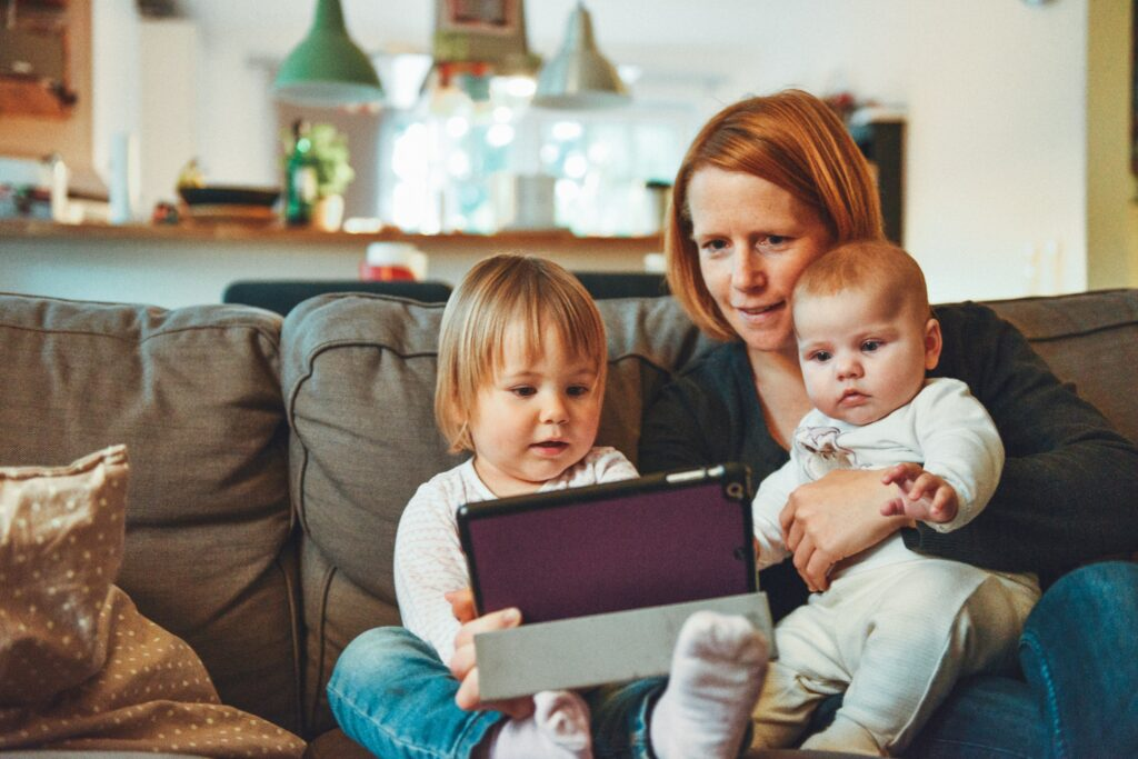En mamma med to et lite barn og en baby som sitter i en sofa og ser på en ipad