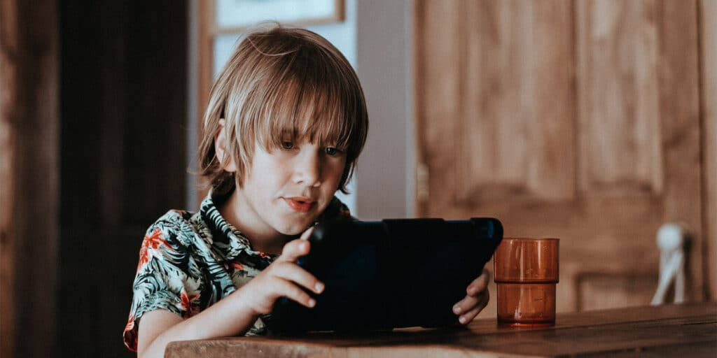 En gutt som sitter å ser ned på en ipad
