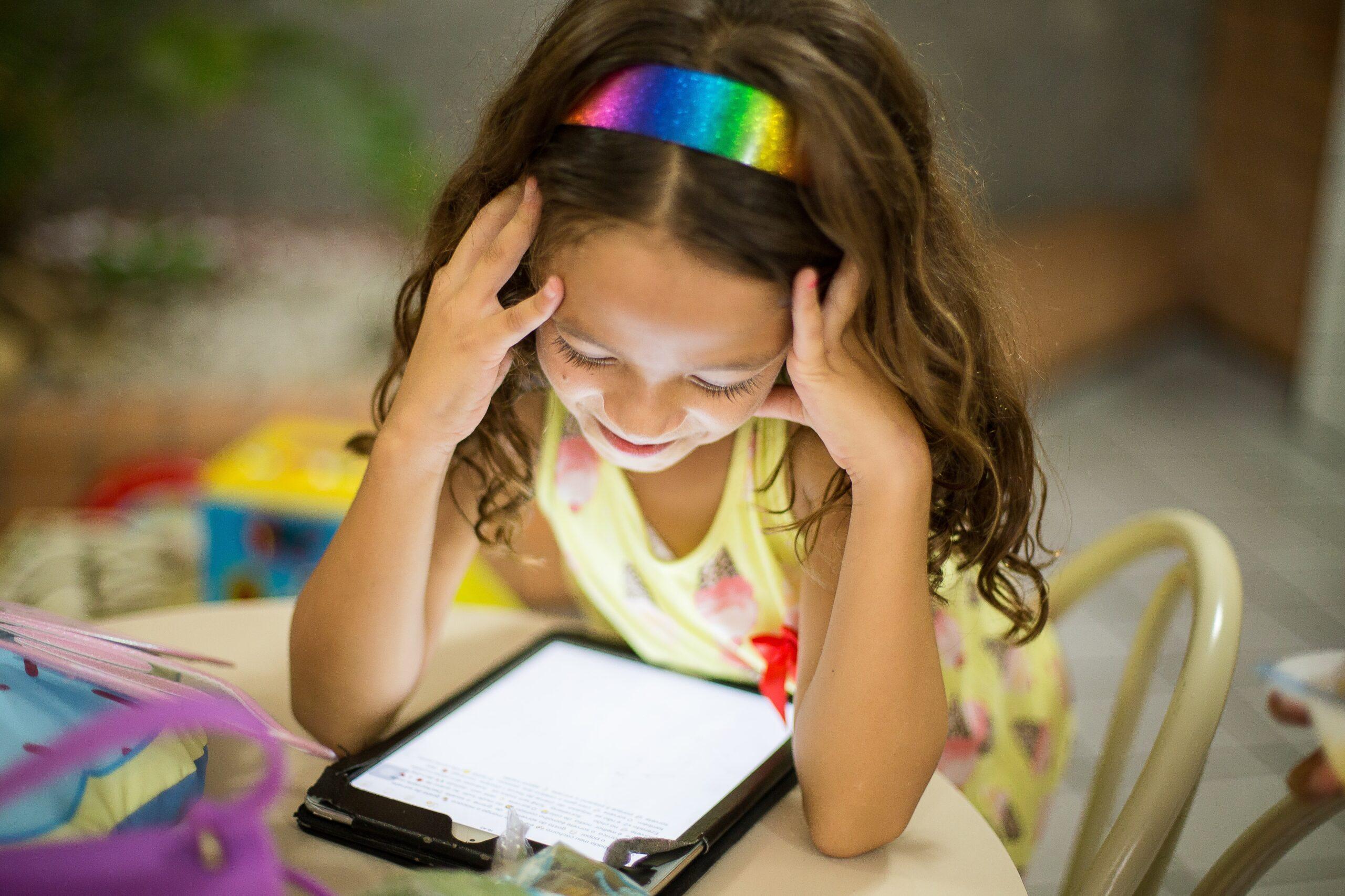 En liten jente med regnbuehårbøyle som ser på et nettbrett