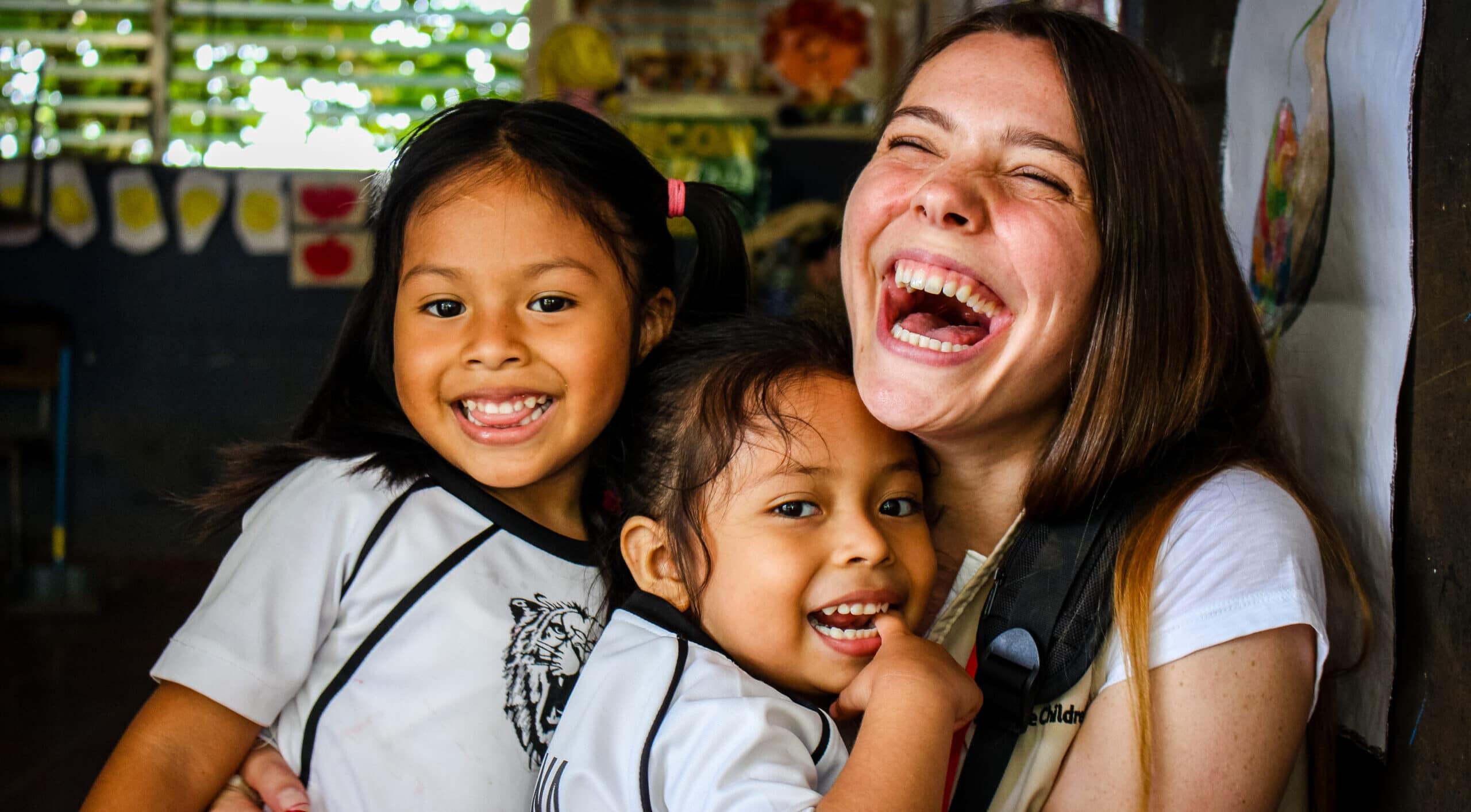 Bilde av en smilende Save the Children-ansatt sammen med barn i El Salvador