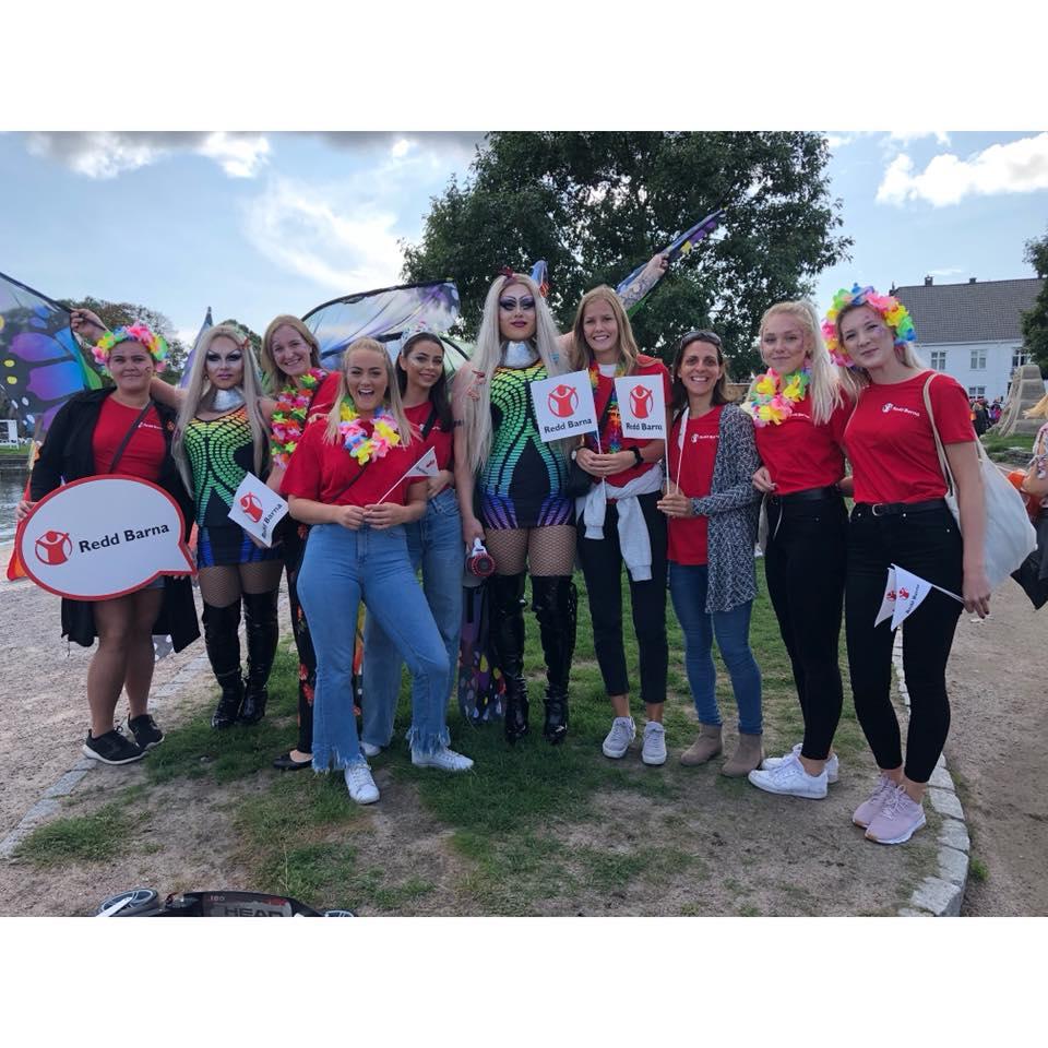 Frivillige fra Redd Barna Kristiansand i røde t-skjorter, fargerik sminke i fjeset og blomsterkranser rundt halsen under Skeive Sørlandsdager